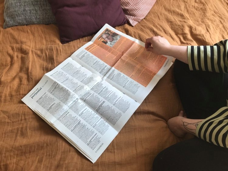 Kuvasta pois rajautuva hahmo lukee Tieteen päivien 2019 ohjelmalehteä.