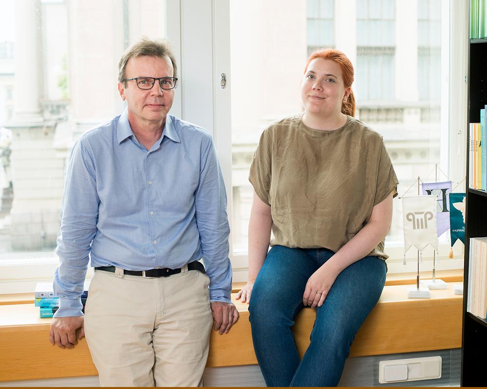 Mandi Vermilä ja Ilari Hetemäki nojaavat neuvotteluhuoneen ikkunalautaan. Taustalla näkyy Kansallisarkisto.